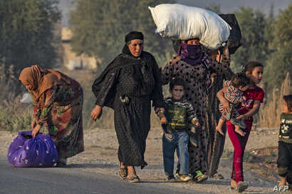 Civilians flee amid Turkish bombardment on Syria's northeastern town of Ras al-Ain in the Hasakeh province along the Turkish…