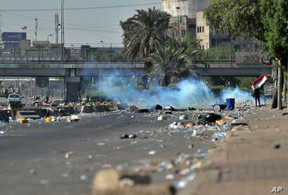 Iraqi security forces fire tear gas while anti-government protesters gather for a demonstration in Baghdad, Iraq, Friday, Oct…