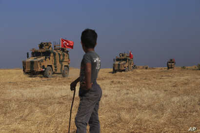 "A Turkish armored vehicles patrol joins a joint ground patrol with American forces in the so-called ""safe zone"" on the Syrian side of the border with Turkey, Oct.4, 2019."