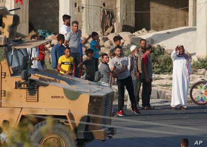 People watch as a Turkish military convoy moves near the border, shortly after the start of a Turkish operation inside Syria,…