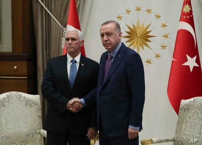 U. S. Vice President Mike Pence, left, and Turkish President Recep Tayyip Erdogan pose together at the presidential palace, in…