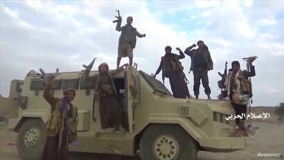 Houthi fighters pose on an alleged captured Saudi vehicle after an attack near the border with Saudi Arabia's southern region of Najran in Yemen, in this still image taken from video on Sept. 29, 2019.