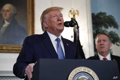 President Donald Trump, accompanied by Secretary of State Mike Pompeo, speaks in the Diplomatic Room of the White House in Washington, Oct. 23, 2019.