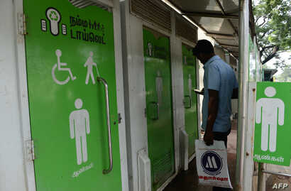 FILE - A man checks his phone as he waits to use a public toilet on a street in Chennai, India, Nov. 15, 2017.