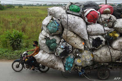 Waste collectors transport plastic scrap for recycling in the suburbs of Hanoi, Vietnam.