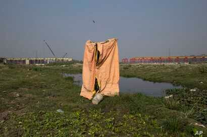 FILE - A make-shift toilet made by farmers for their use is seen near the River Yamuna, in New Delhi, India, Nov. 19, 2015.