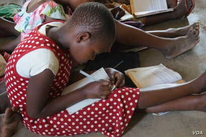Not an easy task, students sitting on a floor at Mazembe Primary School as a result of poor infrastructure perpetuated by a boom in primary school enrollment. (L. Masina/VOA)
