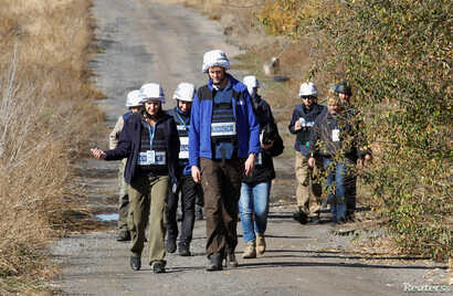 FILE - Members of the Organization for Security and Cooperation in Europe (OSCE) Special Monitoring Mission to Ukraine walk as they arrive for monitoring ahead of a proposed withdrawal of troops, in Petrіvske, Donetsk region, Ukraine, Oct. 9, 2019.