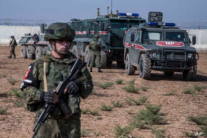 Turkish and Russian patrol is seen near the town of Darbasiyah, Syria, Friday, Nov. 1, 2019. Turkey and Russia launched joint…
