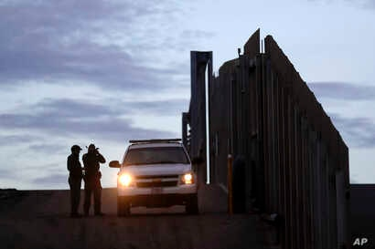 FILE - In this Wednesday, Nov. 21, 2018 file photo, United States Border Patrol agents stand by a vehicle near one of the…
