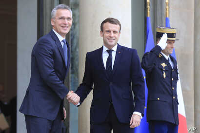 NATO Secretary General Jens Stoltenberg, left, is welcomed by French President Emmanuel Macron at the Elysee Palace in Paris, Nov. 28, 2019.