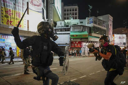 FILE - A journalist records video of a riot police officer charging towards protesters during a clash in Hong Kong, Oct. 21, 2019.