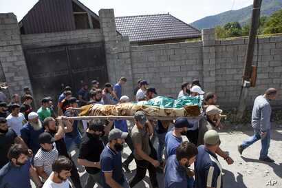 People carry the body of the victim who has been identified as Zelimkhan Khangoshvili, a Georgian Muslim who fought against Russia in the Second Chechen War during the funeral in Duisi village, the Pankisi Gorge valley, in Georgia, Aug. 29, 2019.