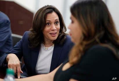 FILE - In this June 14, 2019, file photo, Democratic presidential candidate Sen. Kamala Harris, D-Calif., left, speaks with…