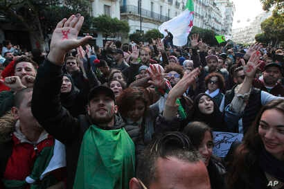 Algerian demonstrators take to the streets in the capital Algiers to reject the presidential elections, in Algeria, Thursday,…