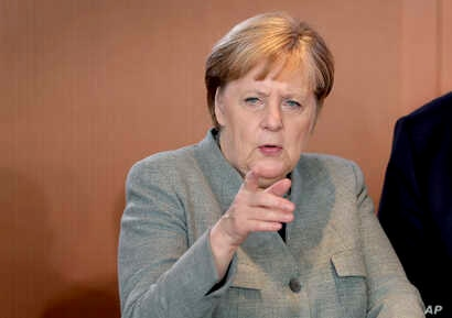 German Chancellor Angela Merkel points as she arrives for the weekly cabinet meeting at the Chancellery in Berlin, Germany,…