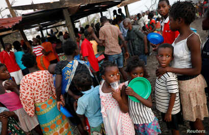 Children queue for food in a camp for people displaced in the aftermath of Cyclone Idai in Beira, Mozambique, March 26, 2019