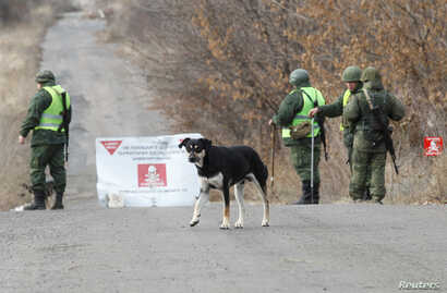 Servicemen of the separatist Donetsk People's Republic stand guard at a checkpoint in the settlement of Petrovskoye (Petrivske), near the contact line with the Ukrainian armed forces in Donetsk region, Ukraine, Nov. 4, 2019.