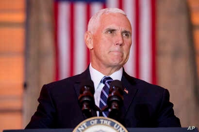 FILE - Vice President Mike Pence pauses while speaking to troops at Al Asad Air Base, Iraq, Nov. 23, 2019.