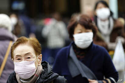 Pedestrians wear protective masks in as they walk through a shopping district in Tokyo Thursday, Jan. 16, 2020. Japan's government…