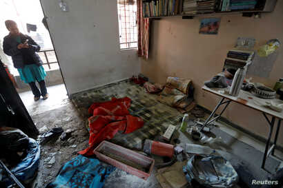A woman stands behind the damaged belongings of students of Jawaharlal Nehru University at a hostel room after it was attacked by a mob, in New Delhi, India, Jan.6, 2020.