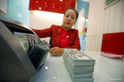 FILE - An employee counts U.S. dollars at a branch of HD Bank in Ho Chi Minh city, Vietnam, Jan. 12, 2018.