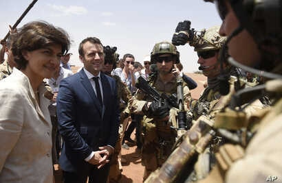 French President Emmanuel Macron, center, and Defense meet soldiers of Operation Barkhane, France's largest overseas military…