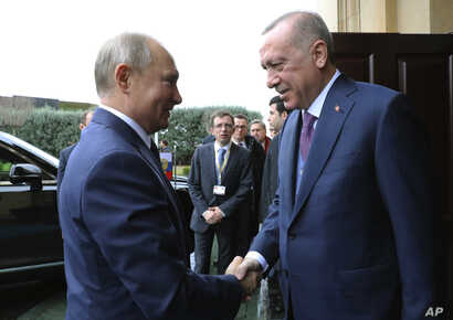 Turkish President Recep Tayyip Erdogan, right, welcomes Russian President Vladimir Putin, in Istanbul, Wednesday, Jan. 8, 2020…