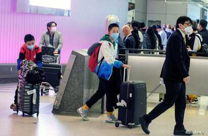 FILE PHOTO: Passengers arrive at LAX from Shanghai, China, after a positive case of the coronavirus was announced in the Orange…