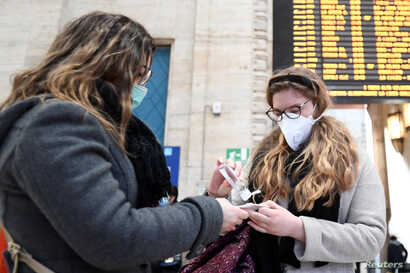 People wearing face masks disinfect their hands at the central railway station, after a coronavirus outbreak, in Milan, Italy, Feb. 24, 2020.