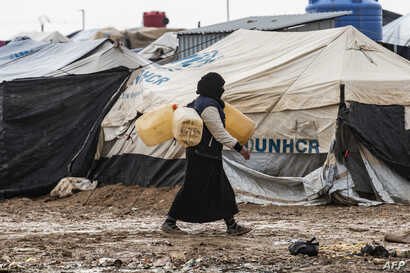A woman carries jerry cans to fill them up with water at the Kurdish-run al-Hol camp for the displaced where families of…