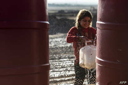 A Syrian girl fills a jug with water in Washukanni camp, on December 16, 2019, which was recently established on the outskirts…