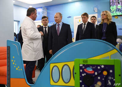 Russian President Vladimir Putin (3rd L) visits a children's clinic during an official trip to Ivanovo, a town some 300 km…
