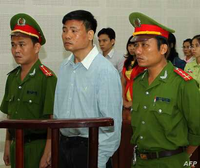 Blogger Truong Duy Nhat (C) stands trial at a local People's Court in the central city of Da Nang on March 4, 2014. Popular…