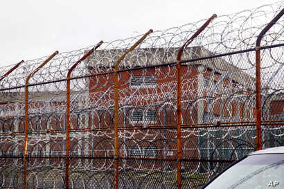 FILE - In this March 16, 2011, file photo, a security fence surrounds inmate housing on the Rikers Island correctional facility…