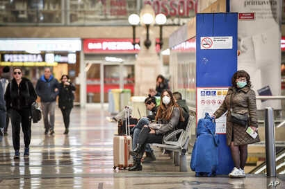 People wear masks as they wait inside Central train station, in Milan, Italy, March 8, 2020.