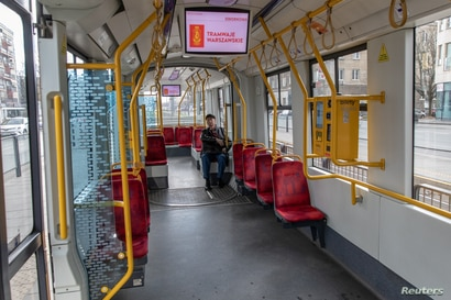 A man sits inside an empty tram amid an outbreak of the coronavirus, in Warsaw, Poland, March 14, 2020.