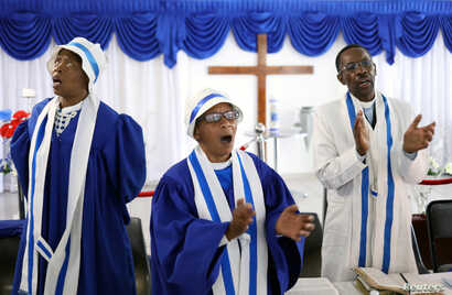 Faithful worship during a church service amid concerns about the spread of coronavirus disease (COVID-19) at the Apostolic Christian Church in Kagiso, west of Johannesburg, South Africa, March 22, 2020.