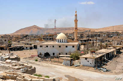 A general view taken on August 13, 2017, shows smoke rising from buildings behind a mosque in the central Syrian town of Al…