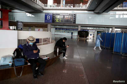 People wearing face masks look at their cellphones at Beijing Capital International Airport, as the country is hit by an…