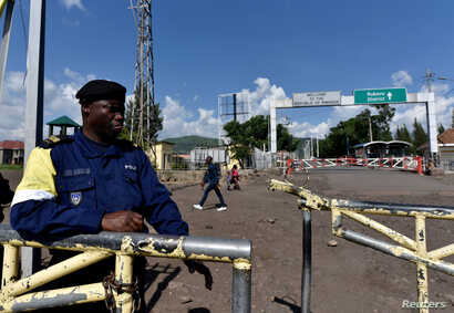 A police officer stands at the deserted crossing point between the Democratic Republic of Congo and Rwanda amid concerns about…