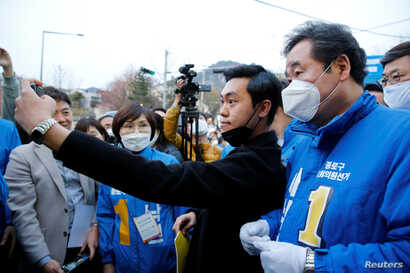 Lee Nak-yon, South Korean former prime minister and a ruling Democratic Party candidate for the parliament, wears a mask to…