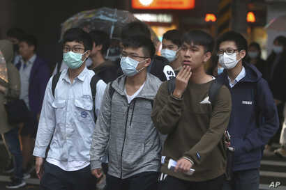 Youths wearing face masks to protect against the spread of the new coronavirus walk on a street in Taipei, Taiwan, Monday,…