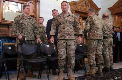 FILE - U.S. Army General Scott Miller, center, commander of U.S. and NATO troops in Afghanistan, is seen at the presidential palace in Kabul, Afghanistan, Nov. 6, 2018.