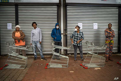 Residents of Yeoville neighborhood of Johannesburg, South Africa, wait in line to enter a grocery store, April 3, 2020.