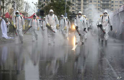 Taiwanese army soldiers wearing protective suits spray disinfectant on a road during a drill to prevent community cluster infection, in New Taipei City, Taiwan, March 14, 2020.
