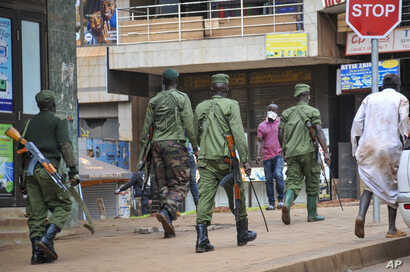 Ugandan police and other security forces chase people off the streets to avoid unrest, as part of measures to prevent the potential spread of coronavirus disease, in Kampala, Uganda, March 26, 2020.