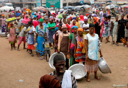 People wait to receive food and water in Accra, Ghana, during a partial lockdown to slow the spread of the coronavirus disease (COVID-19), April 4, 2020.