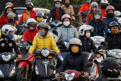 Labourers wearing protective masks wait for a ferry on the way home after work, despite a government rule on social distancing during the coronavirus outbreak in Hai Duong province, Vietnam, April 7, 2020.