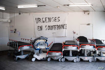 "A picture taken on April 3, 2020 shows a banner reading ""Emergency services are suffering"" above empty stretchers in the hall…"